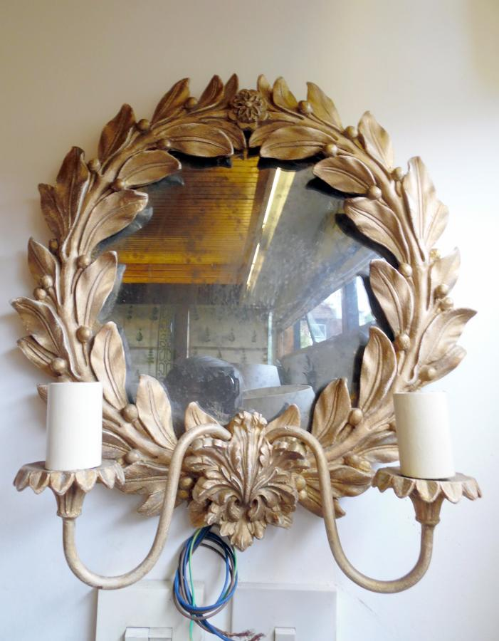 Mirrored wall sconce with gilded leaves