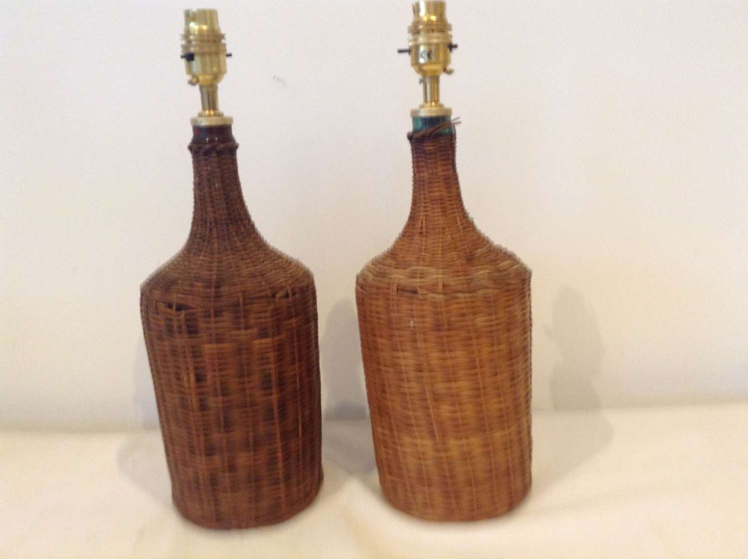 Pair wicker covered glass bottle lamps